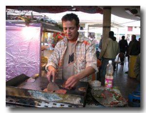 肉の鉄板焼きを焼いている人