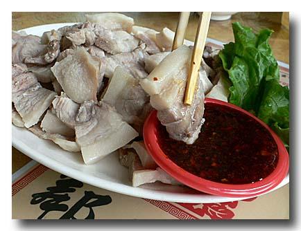 蒜泥白肉 ゆで豚バラ肉の大蒜ソース ソースに肉をつけるところ